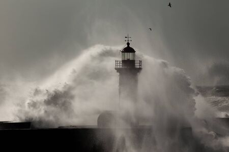Stormy day at the Douro River mouth seeing its old lighthouse covered by spray and moisture from the splash of the waves Stockfoto