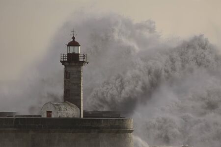 Big wave splash over Douro river mouth old lighthouse, Oporto.