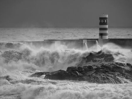 Black and white seascape. Douro river mouth south pier and beacon.
