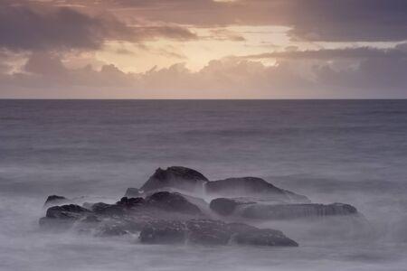 Sea rocks long exposure at orange dusk. Reklamní fotografie - 148277033