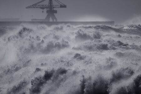 North wall of Leixoes harbor during heavy storm seeing his iconic old huge crane, northern portuguese coast.