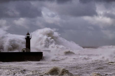 Big white waves over piers and lighthouse against a stormy dark cloudy sky. Douro river mouth, Porto, Portugal.