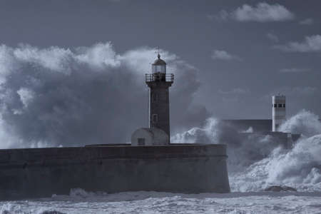 Stormy seascape. Big wave splash over Douro river south piers and beacons, Porto, Portugal. Used infrared filter.