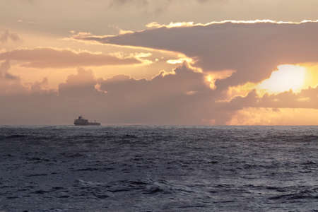 Oil tanker at cloudy red sunset