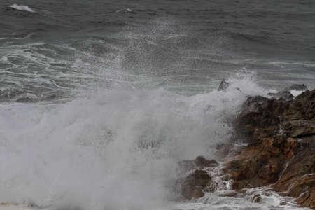 Sea wave breaking over rocks. Northern portuguese coast.