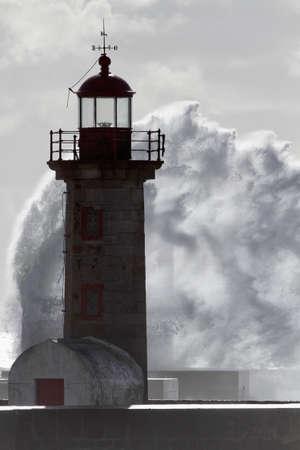 Soft backlit old lighthouse and big wave splash
