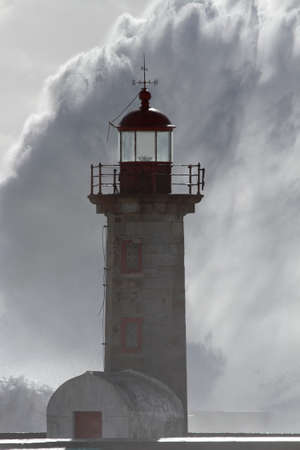 Soft backlit old lighthouse in a stormy dark day seeing a huge wave splash in the background.