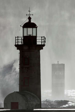 Dark storm in the old Douro river mouth lighthouse seeing wind spray and droplets after a big wave splash
