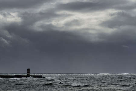 Autumn seascape before rain and storm. Pier and beacon from northern portuguese coast. Stockfoto