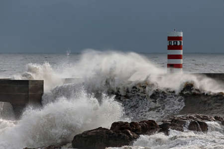 Sea wave spray and splash in the Douro river new south pier and beacon in a stormy evening.