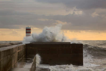 Wave splash at sunset. Douro river mouth new south pier and beacon, Porto, Portugal.