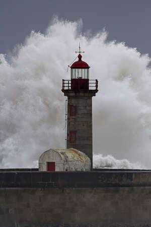 Big stormy wave splash. Old lighthouse from the Douro river mouth, Porto, Portugal.