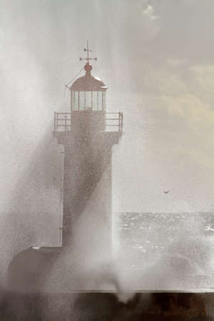 Old lighthouse at the mouth of the Douro River in semi backlight seeing the light filtered by the drops of salt water after a splash of wave Stockfoto