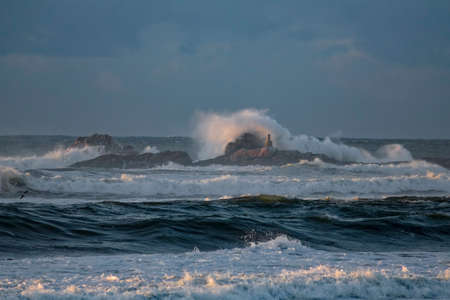 Dark seascape with wave splash at sunset or dusk