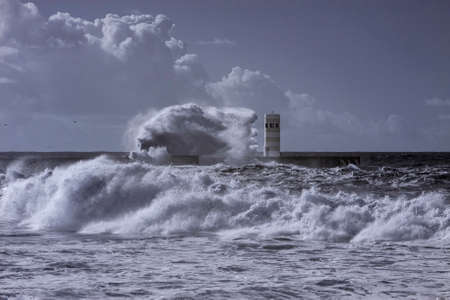 Heavy storm. Douro river north pier and beacon. Used infrared filter. Toned blue. Stockfoto