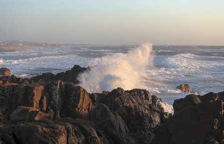 Saint Paio beach cape in a stormy but sunny sunset seeing big wave splash
