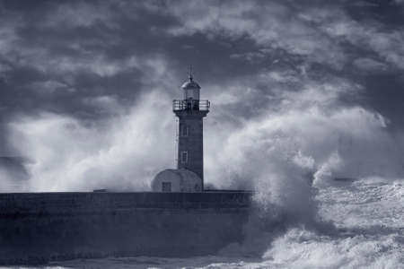 Big wave splash. Douro river mouth old south pier and beacon. Used infrared filter. Toned blue.