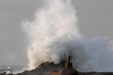 Big sea waves splash over cliffs seeing geodetic landmark. Northern portuguese rocky coast.