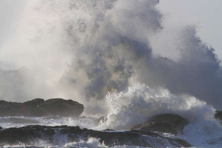 Storm on the coast seeig big wave breaking over rocks and cliffs seeing splash and spray.