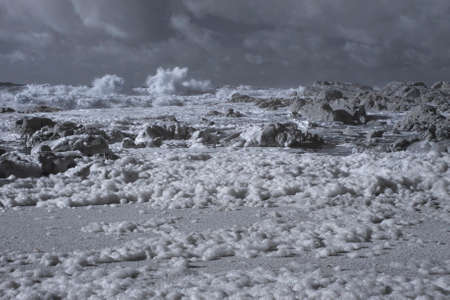 Rocky beach during winter, north of Portugal. Used infrared filter. Focus on the sea foam from the foreground.