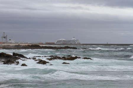 Leixoes harbor north wall and Leça da Palmeira beach during a rough sea day seeing a passenger ship
