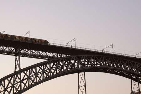 Backlit D. Luis bridge at dawn seeing a train passing, Porto, Portugal. Archivio Fotografico