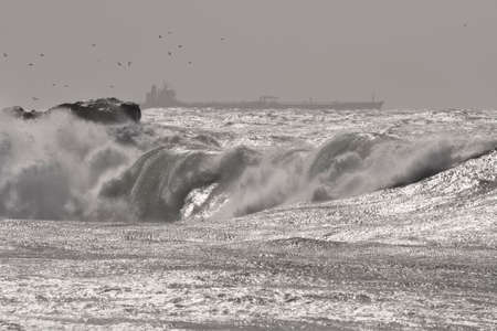 Glistening stormy seascape with powerfull wave and an oil tanker on the hoeizon.