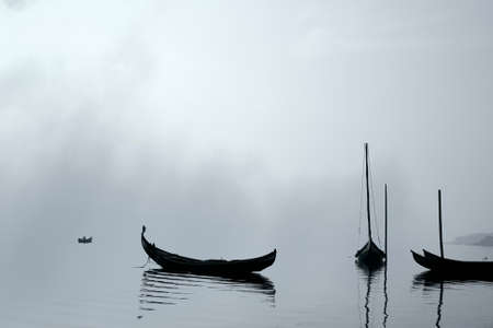 Backlit traditional fisherman wooden boats from Ria de Aveiro, Portugal, in a foggy morning. Archivio Fotografico