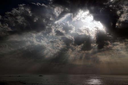 Dramatic cloudy sky with a hole and sunbeams over calm sea