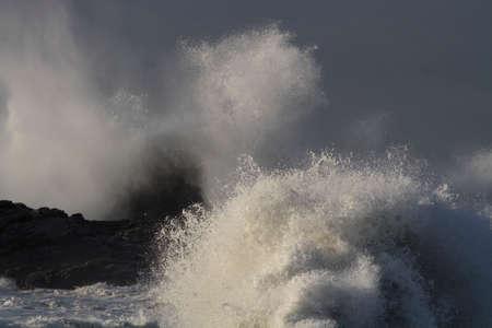 Storm on the coast seeig waves breaking over rocks and cliffs seeing big splash: Focus on the forground splash. Archivio Fotografico