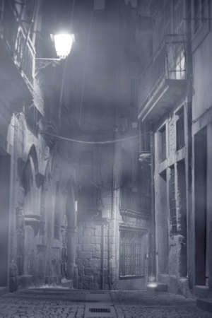 Old Oporto narrow street in a foggy night. Converted black and white and toned blue.