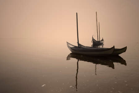 Aveiro ria in a foggy and overcast evening seeing traditional wooden boats, Portugal. Archivio Fotografico