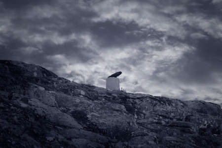 Peneda Geres National Park hill with a crow on a geodetic landmark against a cloudy sky. Black and white toned blue.