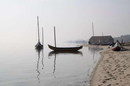 Traditional fisherman wooden boats from Ria de Aveiro, Portugal, in a foggy morning. Archivio Fotografico