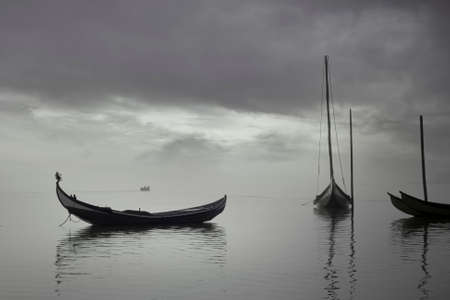 Aveiro ria in a foggy and overcast morning seeing traditional wooden boats, Portugal. Imagens