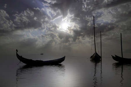 Aveiro ria in a cloudy morning with sunbeams seeing backlit traditional wooden boats, Portugal. Imagens