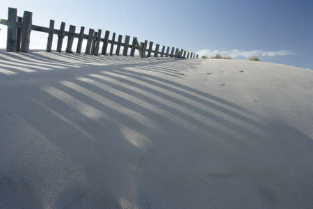 Sand dune and fences with shadows