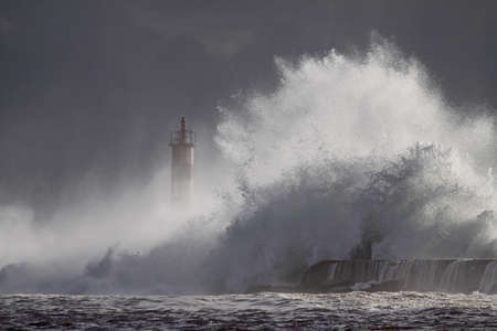 Stormy wave splash. Ave river mouth pier and beacon, Vila do Conde, north of Portugal.