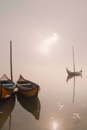 Aveiro ria in a foggy and overcast morning seeing traditional wooden boats, Portugal.