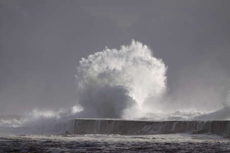 Stormy wave splash. Ave river mouth pier and beacon, Vila do Conde, north of Portugal. Archivio Fotografico