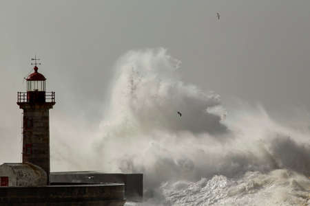 Old lighthouse and pier of Douro river mouth under heavy storm with big splashing waves.