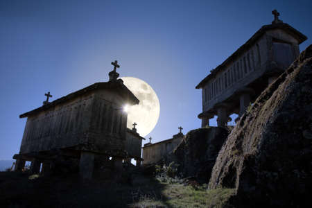 Mysterious Soajo granaries (old typical granite granaries of northern Portugal) on a rising full moon at dusk.