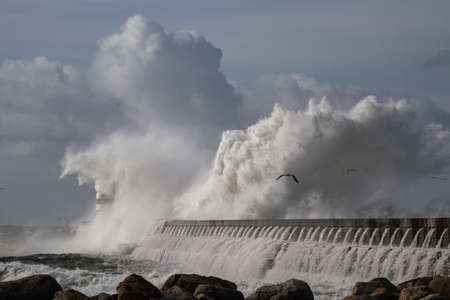 Winter seascape. Douro river north pier and beacon during storm, Porto, Portugal.
