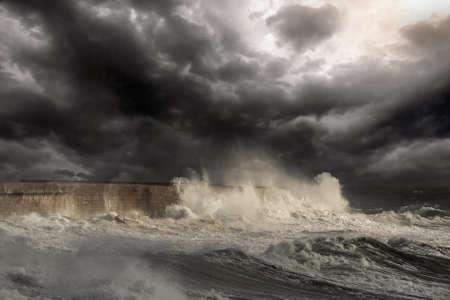 Dramatic sea scene with big white waves crashing against the harbor wall of Leixoes, near Porto in Portugal. Enhanced sky. Archivio Fotografico