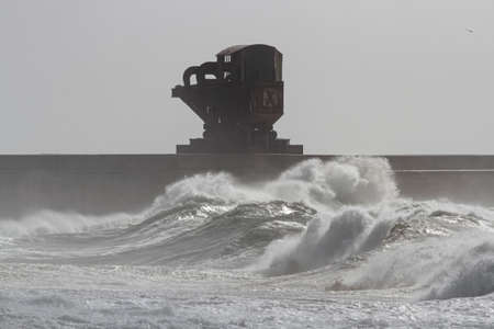 Leixoes harbor north wall durin g storm seeing the old huge iconic Titan crane. Archivio Fotografico