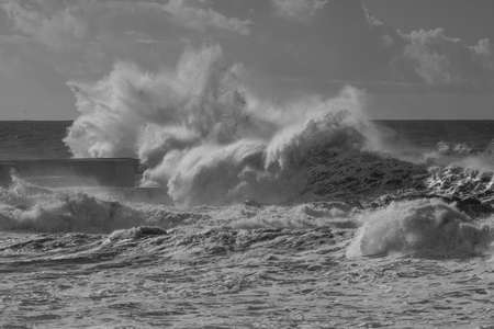 Black and white stormy seascape. Douro river mouth north pier, Porto, Portugal. Used infrared filter.