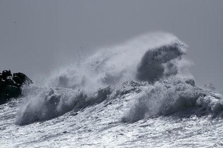 Big wave splash in a rough sea day. Toned blue.