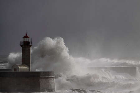 Old Duro river mouth lighthouse during storm with beautiful light before rain, Porto.