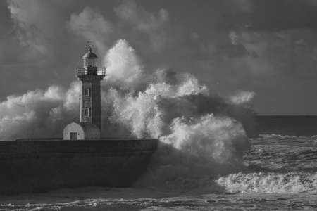 Big wave splash at the Douro river mouth old pier and lighthouse. Black and white. Infrared.