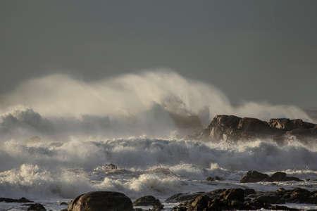 Big stormy waves with wind spray. Northern Portuguese rocky coast. Archivio Fotografico